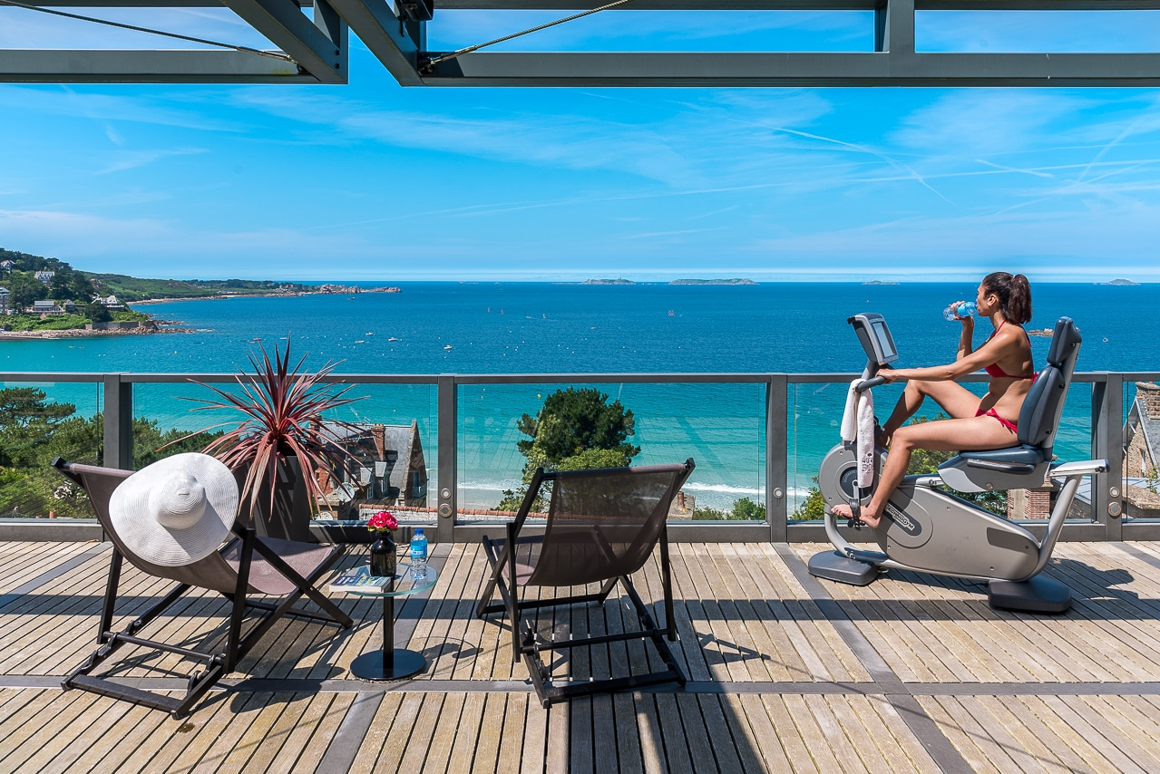 Jeune femme faisant du sport sur la terrasse  avec magnifique vue sur mer