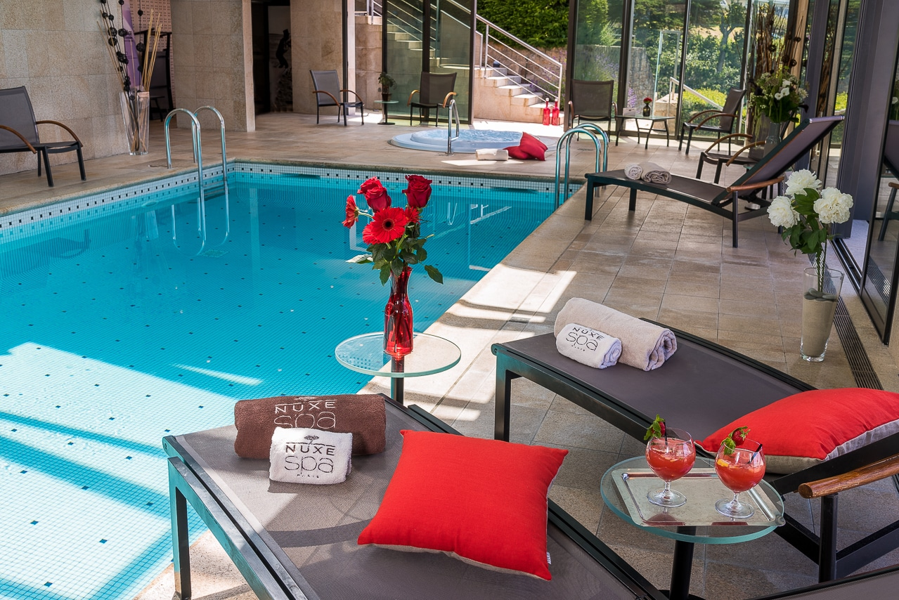 Transat avec serviettes Nuxe à côté de la  piscine