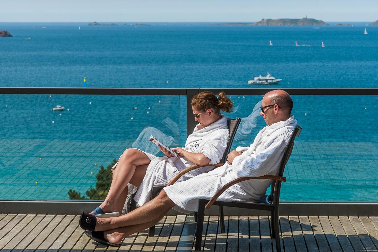 Couple bronzant sur les transats de la terrasse