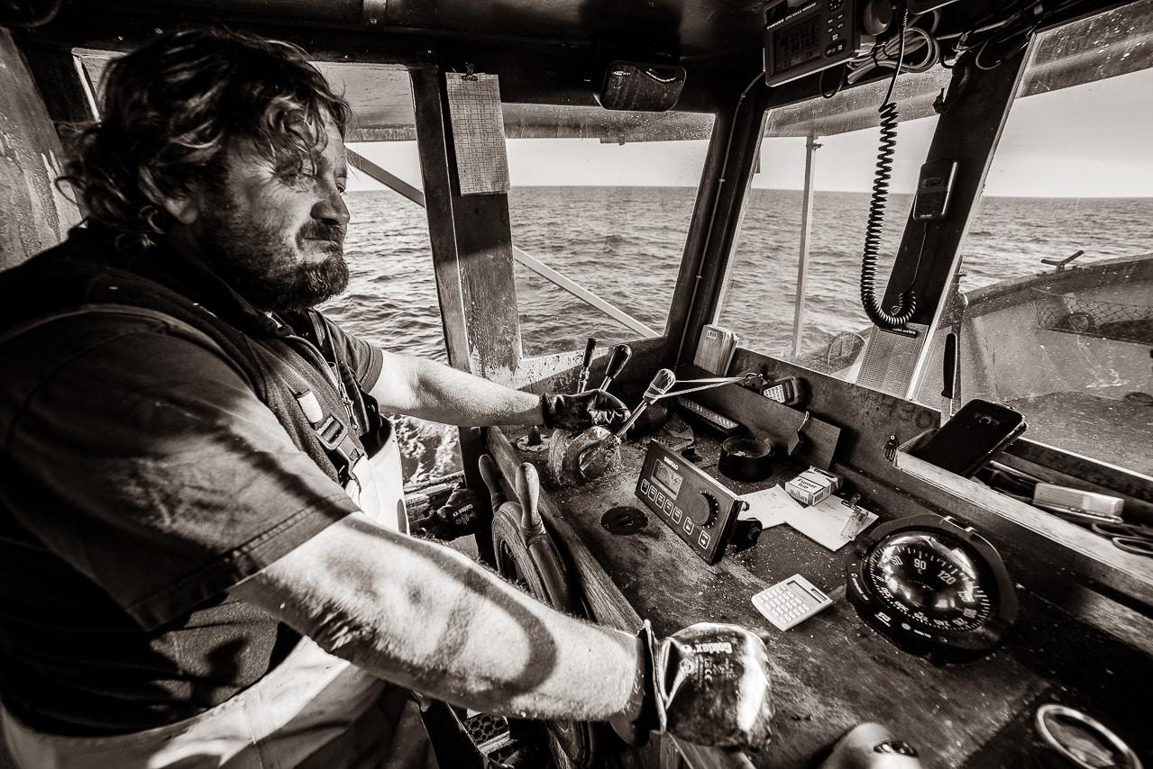 Portrait d'un pêcheur en noir et blanc à la barre