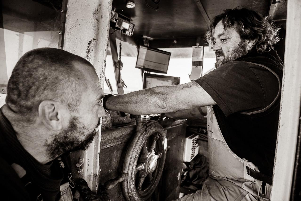 Portrait Noir et blanc de deux pêcheurs parlant à la barre