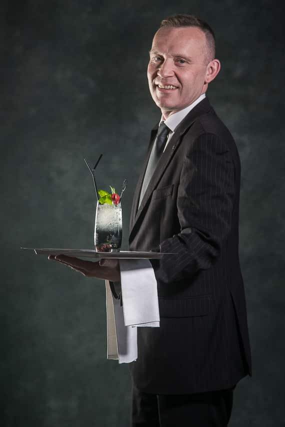 Portrait d'un serveur avec cocktail sur son plâteau